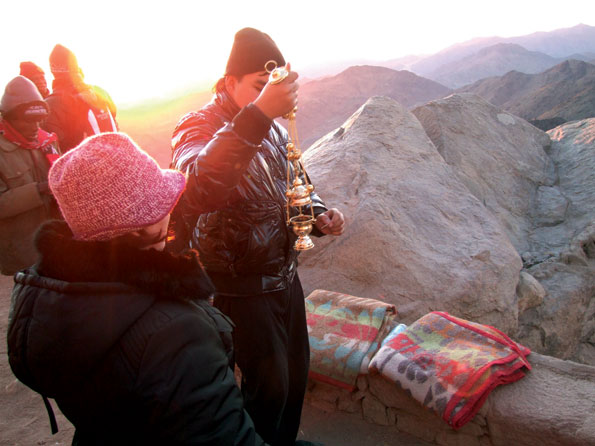Er wordt gebeden op de top van de Sinaï terwijl de zon opkomt.